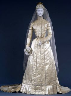 Wedding dress, Hirsch & Co., Dresden, 1900. Ivory silk satin, 2 pieces. Bodice fitted in back, skirt straight in front with pleats that create volume in back, pleated flounce. Embroidered on bodice, collar, cuffs, and top of sleeves with applications of satin ribbon in patterns of bows and connected by silk cord. Galleria del Costume di Palazzo Pitti via Europeana Fashion