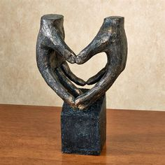 The Heart in Hands Table Sculpture conveys a message of love with a universally known symbol. We find symbols in all facets of life, and perhaps the strongest symbols we see are those that signify love.