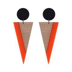 Brinco longo com base de acrílico preto redonda e pingente de acrílico em formato de triângulo invertido na cor laranja com detalhe sobreposto em laminado de madeira clara. Medidas do brinco (AxL, incl. base): 9,5 x 3,5 cm.Referência: V17-826Esse ...