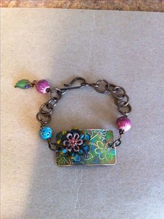 Etched brass component, with enameled petal flowers and accent enameled beads.Vintaj jump rings .