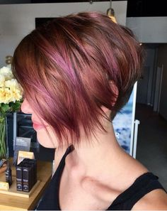 Violet and pink highlights play up this fun red hair color created by @ardentjourney at @amartesalon. We love the angled bob with messy texture. Aveda color formula in comments.
