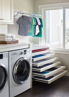pull out drying racks are hidden behind white drawer fronts accented wit., Stacked pull out drying racks are hidden behind white drawer fronts accented wit., Stacked pull out drying racks are hidden behind white drawer fronts accented wit. Laundry Room Drying Rack, Drying Room, Clothes Drying Racks, Laundry Closet, Laundry Room Organization, Small Laundry, Drying Cupboard, Hidden Laundry, Laundry Rack
