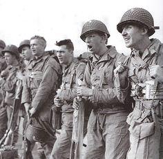 England june 1944. Ces hommes qui chantent un cantique à bord d'un navire sont des Engineers identifiables grâce au cercle blanc peint sur les casques. Ils seront chargés de détruire les obstacles présents sur la plage d'Omaha . En prévision de la traversée les fusils sont placés dans un sac étanche et ces hommes portent tous la ceinture de sauvetage. Ces troupes vont payer un lourd tribu en abordant la plage en premier, obligés d'effectuer leur mission sous les tirs ennemis.