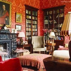 Room of the Day ~ patterns in red mix playfully in this warm library in Georgian house in Ireland.  Paisley on ottoman, large print on wallpaper & black mantle. 4.27.2014