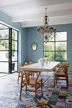 Blue Dining Room with Wishbone Chairs and Concrete Tiles in dining room design ideas - modern dining room with glass chandelier and graphic floor tiles.