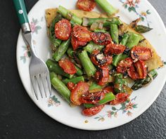 A chickpea pancake topped with roasted tomatoes, asparagus, and onions.