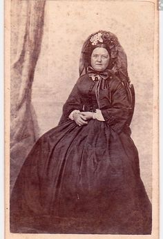 Mary Todd Lincoln, wife of President Abraham Lincoln. Dressed in mourning as was the custom of those days. After willie's death, 1862-63       The white flowers in her bonnet  symbolized the death of her son.  P.S.  Some people of this age are so judgmental at what they do not know !