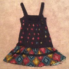 FP funky tunic Black with vibrant red, orange, gold, blue. Lace accents.m mesh lined. Outside fabric is acrylic with a touch of wool. Third pic show a few loose threads on the front just below the strap. Hardly noticeable but easily trimmed or tied off. Free People Tops