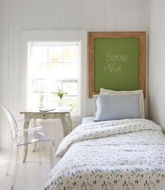 With not an inch to spare, the owner of this Florida cottage pushed the guest room's twin bed against the wall and hung a green chalkboard in place of a headboard. Bonus: The piece doubles as a memo board.   - CountryLiving.com