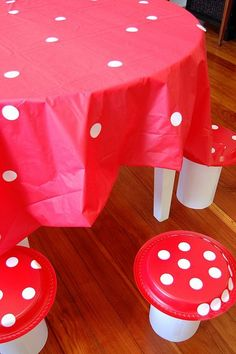 I purchased a plastic table cloth at the dollar store and the girls and I covered it with white circle labels from Office Depot.    The stools are made from boxes of oatmeal covered with white paper. Then we taped red plates, from the dollar store, on top and covered them with more white labels.