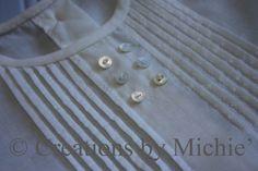Tiny tucks and tiny buttons