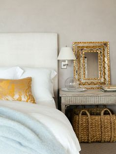 Muted grey painted bedroom walls with shots of colour in the mustard pillow and pastel blue throw on the bed.  Great storage idea with an over-sized rattan basket underneath the bedside table.  Too much to love in this picture!