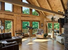 This beautiful open great room of a Hochstetler Log Home features a cathedral ceiling, exposed beams, and plenty of windows to let in natural light. This is a modified Pleasant Hill floor plan. #loghome #logcabin #exposed beams