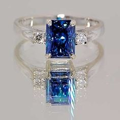 Platinum ring with emerald-cut blue sapphire and diamond accents