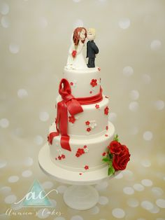 Blossom Wedding cake White and red and modeled figurines and red sugarroses.  Bloesem rood en wit bruidstaart met geboetseerd bruidspaar en suikerwerk rozen.