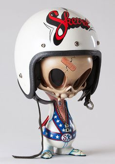 "ARTIST: Jay Hollopeter TITLE: Skevel Knievel SIZE: 19"" Tall (With Helmet) MEDIUM: Mixed Media with Vintage Helmet PRICE: $900"