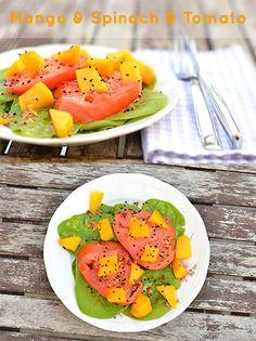 Salat vom Baby-Spinat mit Fleischtomaten und Mango an Arganöl-Passionsfruchtessig-Ingwer-Vinaigrette getoppt mit Schwarzkümmel