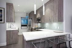 In this article, we go over the top two natural stone options to consider when remodeling your kitchen and the benefits of using natural stone when designing kitchen islands. Kitchen Cabinet Colors, Kitchen Colors, Design Kitchen, Modern Pendant Light, Pendant Lights, Dark Wooden Floor, Gray Cabinets, Glass Cabinet Doors, Interior Decorating