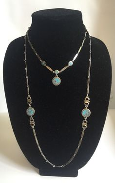 These two Sarah Coventry necklaces were made to be worn together (or stacked together)! They are in excellent vintage condition. These necklaces lay flat and the faux turquoise stones are flat. You can wear these day or night to complete any outfit!  The first smaller necklace is approximately 16 inches long with 3/4th an inch flat silver-like chain. In the center of the necklace there are 3, 1/8th inch round faux stones surrounded by sliver-like metal. Dangling from the center faux…
