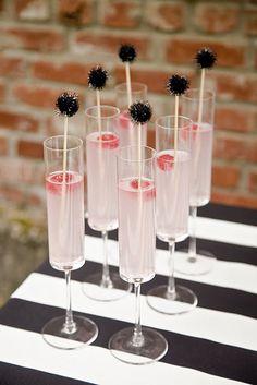 Pink champagne, pop stir sticks and a raspberry garnish.