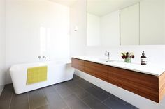 Floating double basin vanity Stand alone bath Cupboards behind mirror
