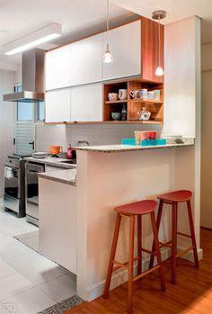 Integrando a cozinha à sala, o balcão americano já existia – apenas recebeu tampo de granito branco polar, que serve de apoio às refeições rápidas. O tom amadeirado do acabamento dos armários, igual ao dos móveis da sala, foi eleito para manter a unidade visual entre os ambientes. Além disso, forma uma bela combinação com o inox dos eletrodomésticos. Banquetas: Sela (46 x 28,5 x 74 cm). Tok Stok, R$ 275 cada. Projeto da arquiteta Daniela Berardinelli.