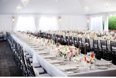 Elegant and crisp - long tables with white linens are decorated with arrangements of roses and charcoal gray candles - charcoal chairs complete the look