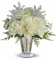 """Teleflora's Winter Glow  Gorgeous white roses, asiatic lilies and miniature carnations are beautifully arranged with magical silver snowflakes and delivered in a glamorous silver Mercury Glass Vase. Glow ahead and send this stunner today!  Approximately 11"""" W x 11 1/2"""" H T133-1A $37.95"""