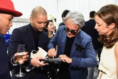 Designer Giuseppe Zanotti signs a shoe @ Giuseppe Zanotti Design Beverly Hills Store Re-Opening on April 14, 2015