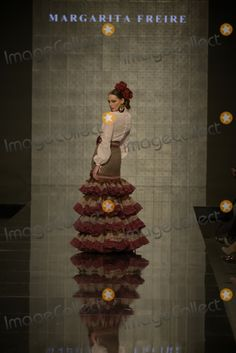 SEVILLA, SPAIN, JANUARY 30, 2014: The model parades on the catwalk displays one of the creations from the collection -Mis Amores- of the Spanish flamenco fashion designer Margarita Freire during the 20th International Flamenco Fashion Salon (Salon International de la Moda Flamenca - SIMOF 2014 ) held in Seville, Spain.