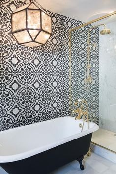 White and black bathroom features an accent wall clad in black and white cement tiles, Cement Tile Shop Bristol Tiles, lined with a black clawfoot tub fitted with a shiny brass vintage hand held tub filler illuminated by a Suzanne Kasler Morris Lantern placed next to a glass and brass shower enclosure.