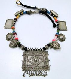 India | Old solid silver necklace from Rajasthan.  Beautiful stamped design house pendant (a symbol of family unit represented by a walled-in rectangle, the amulet uses stamped floral units to cover joins) strung together with many different tribal silver pendants and beads on colorful yarn.
