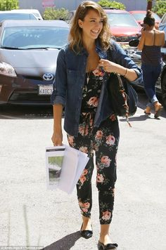 Jessica Alba in a black romper suit with a colorful pattern of pink roses