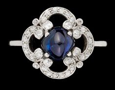 An 18k gold and platinum ring set with a sugarloaf cut blue sapphire and diamonds, ca. 1926.