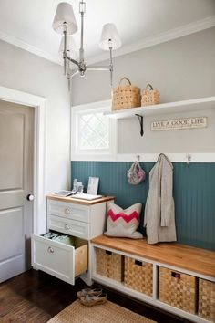 TerraCotta Properties  Adorable mud room with gray walls paint color, beadboard walls painted peacock blue, hooks, wood storage bench with baskets, seagrass rug, white floating shelf, polished nickel chandelier and gray painted door.