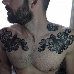 Tatuaje de ornamentos de estilo barroco en cada pecho, y un tatuaje de una corona junto al cuello. Artista tatuador: Alex Bawn