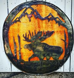 Moose cutout inlaid into a wine barrel ring with wood inserted behind it.