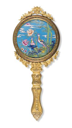 AN ENAMELLED GILT-BRONZE HAND MIRROR QING DYNASTY, 18TH – 19TH CENTURY of circular form, the reverse enamelled with a pair of confronting phoenix, all framed within a copper border, between gilt-bronze foliate sprigs of stylised florets, and further embellished with coloured stones, rising from a handle similarly decorated with a floral design beneath the character shou ('longevity')