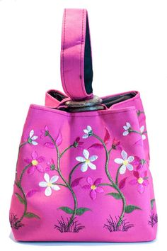 """Square shape with 3 wooden rings to weave handles through. Made of silk and embroidered with silk thread. The wristlet can easily fit your basic necessities. Would also make a great gift bag for someone special. Measures 6"""" tall by 6""""s wide. Handle measures 7"""" long. Available in pink or green. Sweet Silk Wristlet by Ottoman Imports. Bags - Clutches Kentucky"""