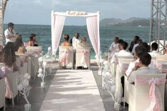 Bamboo arch , decorated with white fabric and pink lace , guirland of white and pink flowers , white carpet  made by www.fee-des-caraibes.com  Face book: Mariages À Saint Martin
