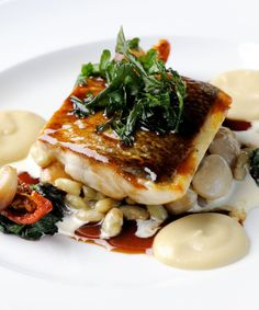 Pan-fried sea bass sits beautifully atop a mound of creamy beans in Mark Dodson's indulgent recipe. A rich Jerusalem artichoke purée and robust red wine jus are perfect accompaniments, while the suggested plating with deep-fried rocket and sun-dried tomatoes would take this dish to another level.