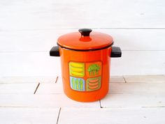 1960s orange enamel stockpot with vegetable graphic on the front.  •Two black metal handles on either side.  •Condition: In great vintage condition.