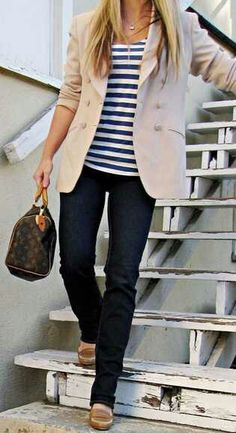 a simple beige blazer over a striped navy blue top
