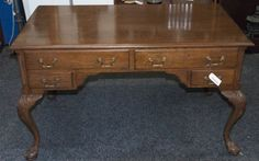 VINTAGE PARTNERS TABLE WITH BALL AND CLAW FEET. THIS OFFICE DESK ACCOMMODATES TWO PEOPLE, ONE SEATED ON EITHER SIDE. AS SUCH, ONLY ONE SIDE OF THE DRAWERS OPEN ON EACH SIDE. THERE ARE FOUR WORKING DRAWERS AND FOUR DUMMY DRAWERS. MEASURES 4 FEET 1 INCH HIGH, 2 FEET 5 INCHES DEEP AND 2 FEET 5 INCHES DEE