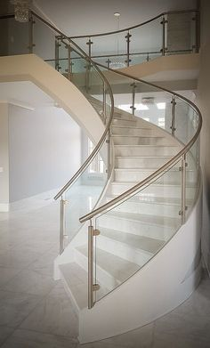 Modern curved staircase with stainless steel and glass railings for clean, clear views. #projectofthemonth