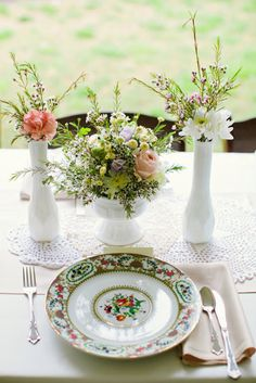 Love this vintage table setting with doilies and delicate flowers in milk glass vases. Amanda Watson Photography. #tablesetting #vintagewedding #milkglass