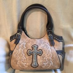 """Western Flair Purse This purse is approximately 14""""x 18"""" - (18"""" from bottom to top of handles when holding in upright position). Dark brown trim.& beige rawhide look in background. Has antique look cross center on front. Cross has a star on each points & centered overlapping horseshoes facing upward. Deep pockets on each side panel. Back has a trimmed & a zippered pocket. 3 large compartments on the inside, middle compartment is a zippered section. Other sections have smaller pockets within…"""