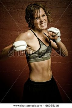 a young and fit female fighter posing in combat poses by Andreas Gradin, via ShutterStock