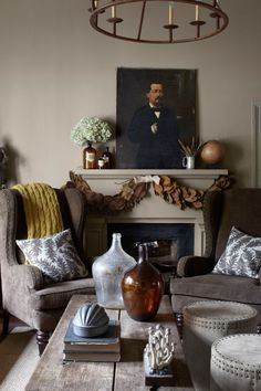 The owner of this Georgia home shopped Stanton Home Furnishings, his own home-goods store, for the living room's corduroy-upholstered wing chairs, fern-print pillows, and antique demijohns. The drum-shaped ottomans are by Lee Industries; the oil portrait dates to the 1860s.