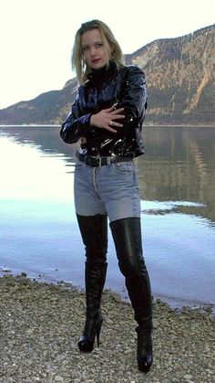 Amateur blonde in black leather jacket jeans thigh boots by water